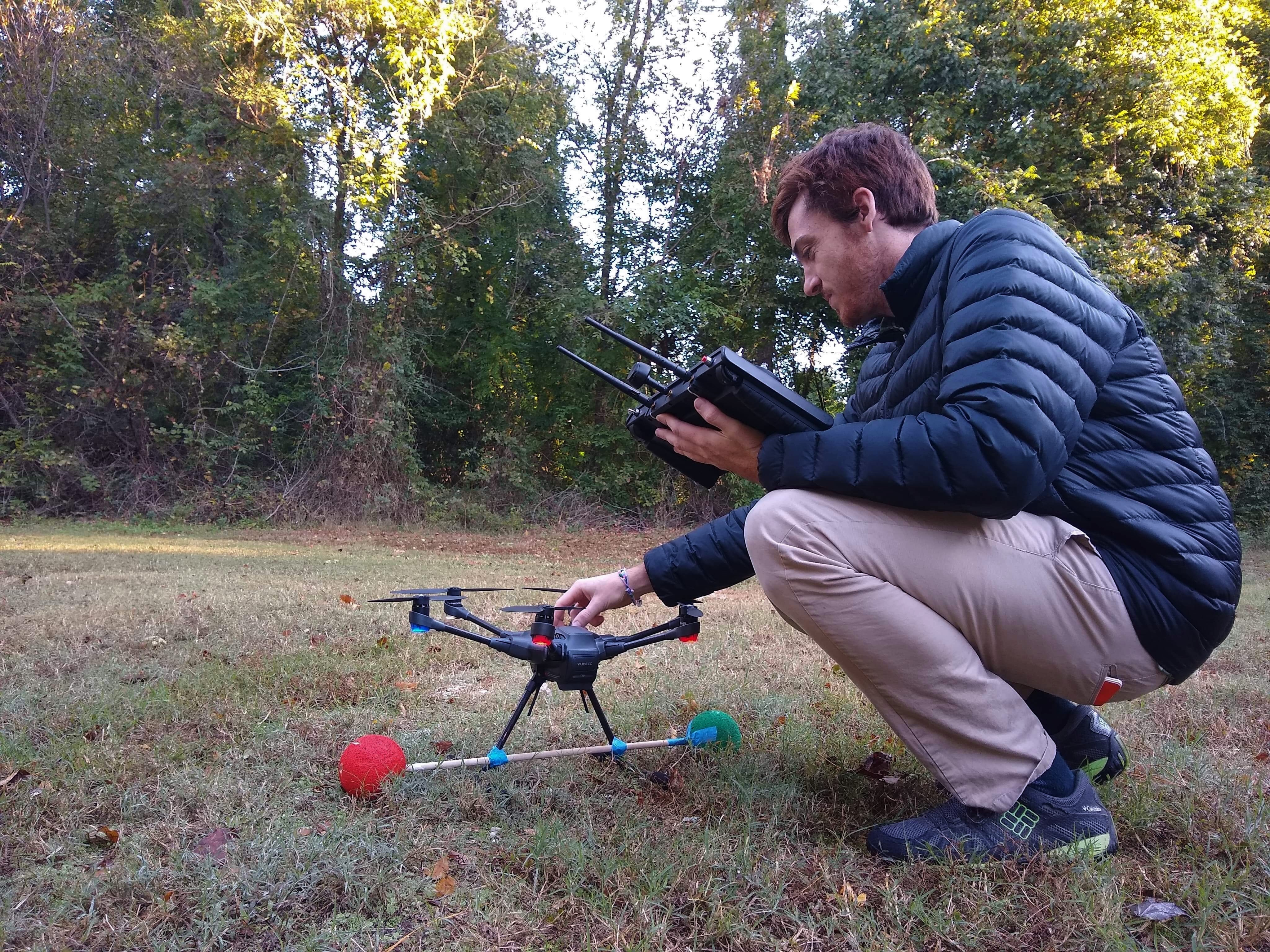 A scientist setting up a drone camera to track birds in flight