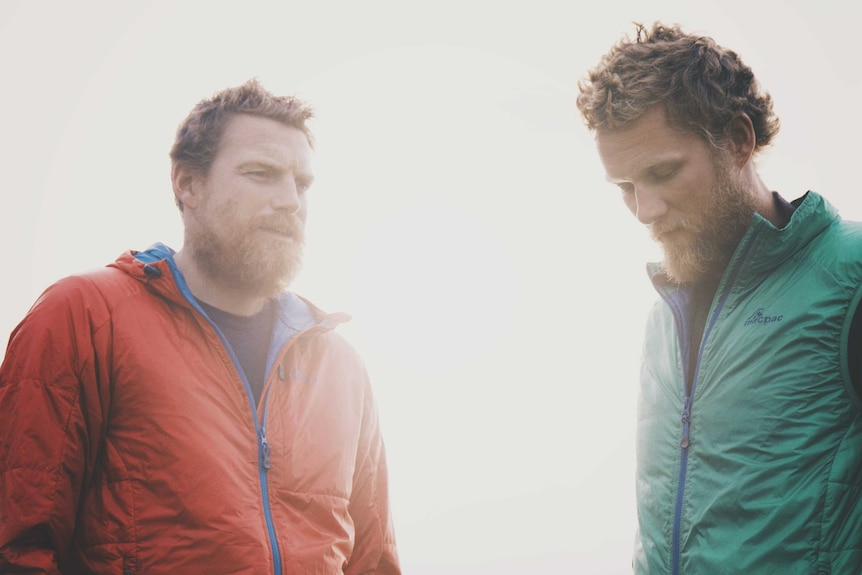 Two men with beards stand together.