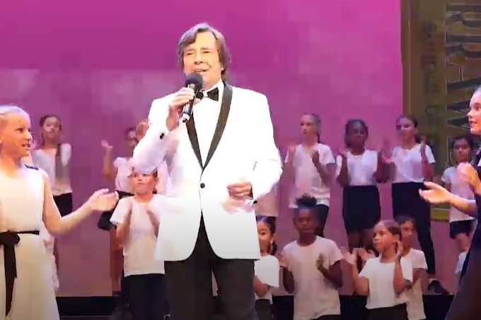 John Paul Young in a white suit on stage with school students performing around him
