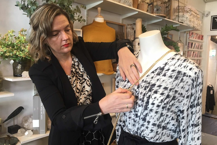 Amber Barnes arranges accessories on a mannequin in her retail boutique in Sydney's inner-west.