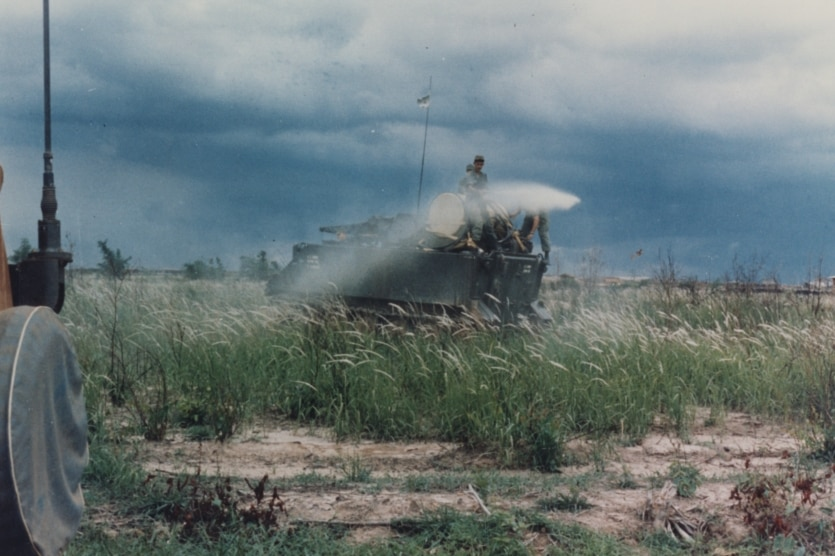 Soldiers on top of a army carriers spraying Agent Orange onto grassland
