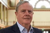 Peter Costello wears a dark jacket and a check shirt