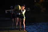 A woman in the Australian Olympic uniform carries out a rowing boat.