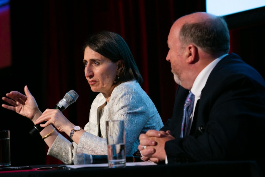 Two people sit as if at a public forum.