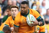 A Wallabies player runs with the ball as the Springboks attempt to tackle him.