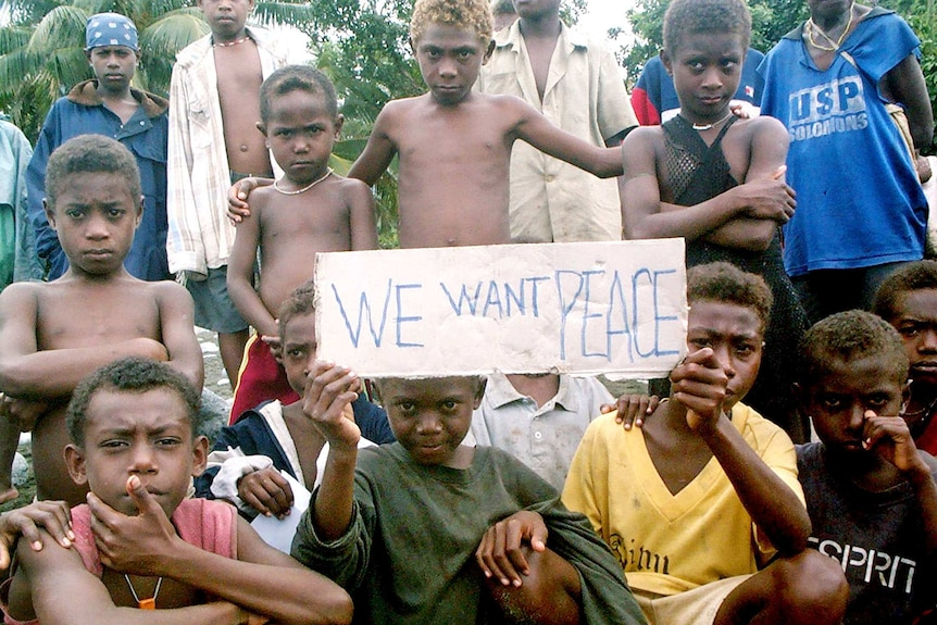 Children hold a sign asking for peace in the rebel stronghold of the Weathercoast, Solomon Islands, July 2003.