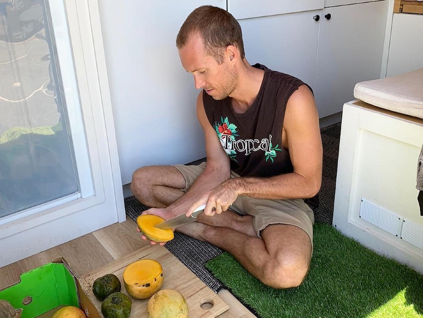 Man sits on the floor of a van chopping up fruit.