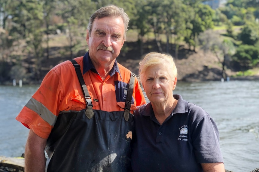 a man in overalls and a woman standing in front of river smiling