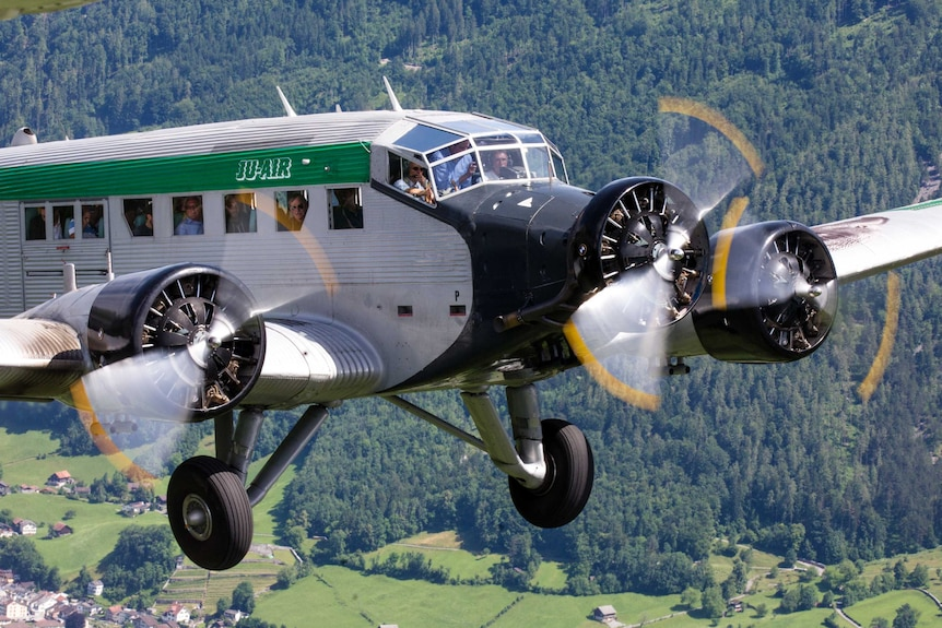 Passengers looking out of the JU-52 aircraft as it flies in the sky.
