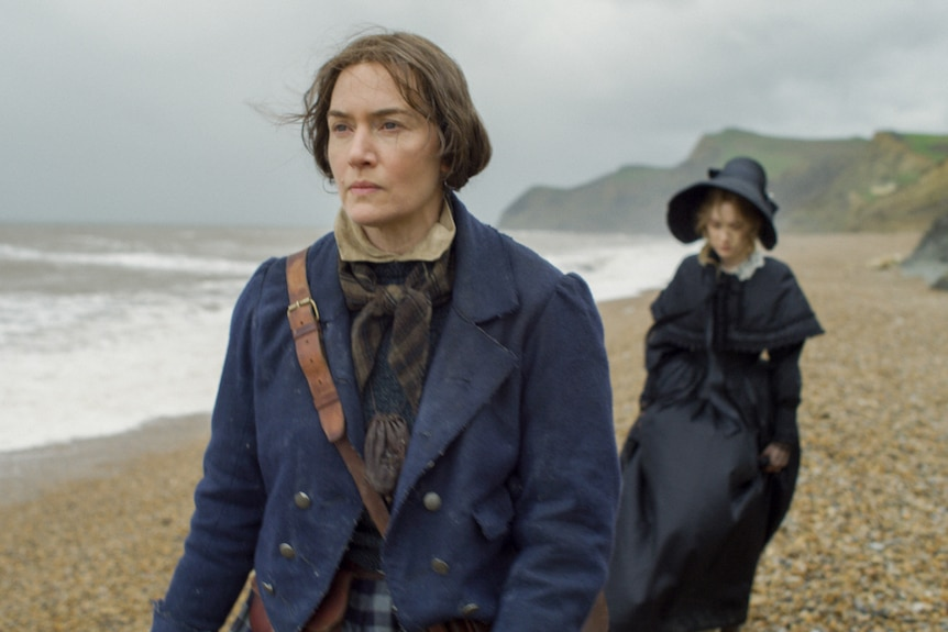 Winslet and Ronan in 19th century clothing walking on overcast beach towards camera, Winslet leading and Ronan lagging behind.