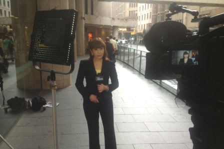 Wells standing in front of camera in street holding a microphone.