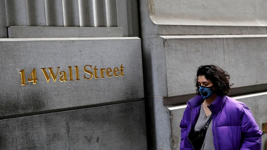 A lady wearing a face mask walks along Wall Street in early March, during the coronavirus pandemic.