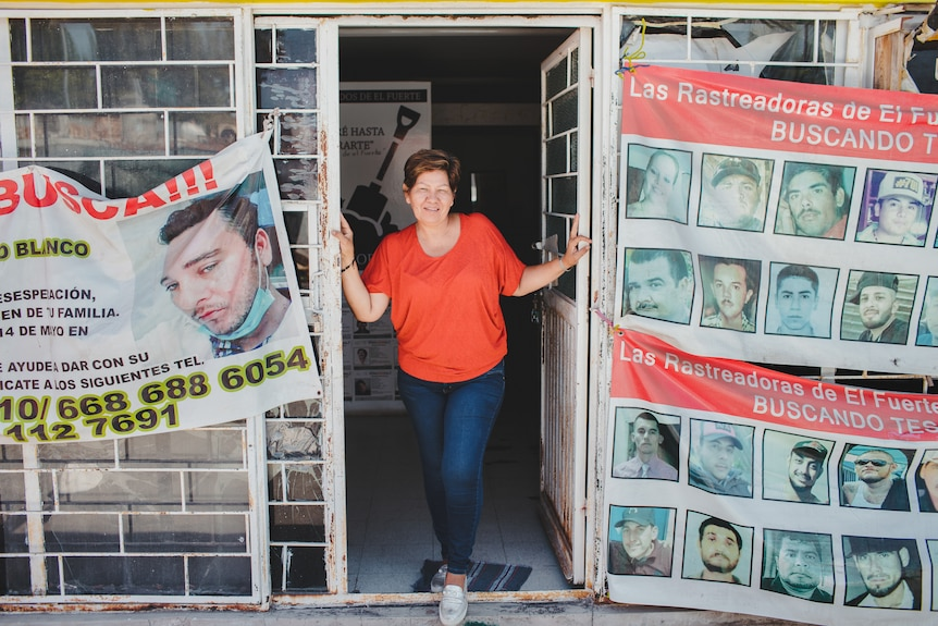 A woman stands in the doorway of an office covered in posters.