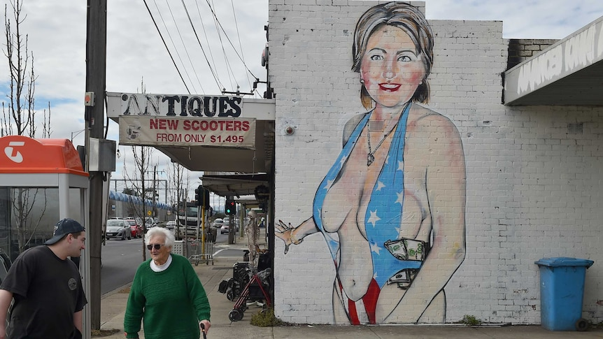 Pedestrians walk past a mural of Democrat US presidential nominee Hillary Clinton clad in a swimsuit