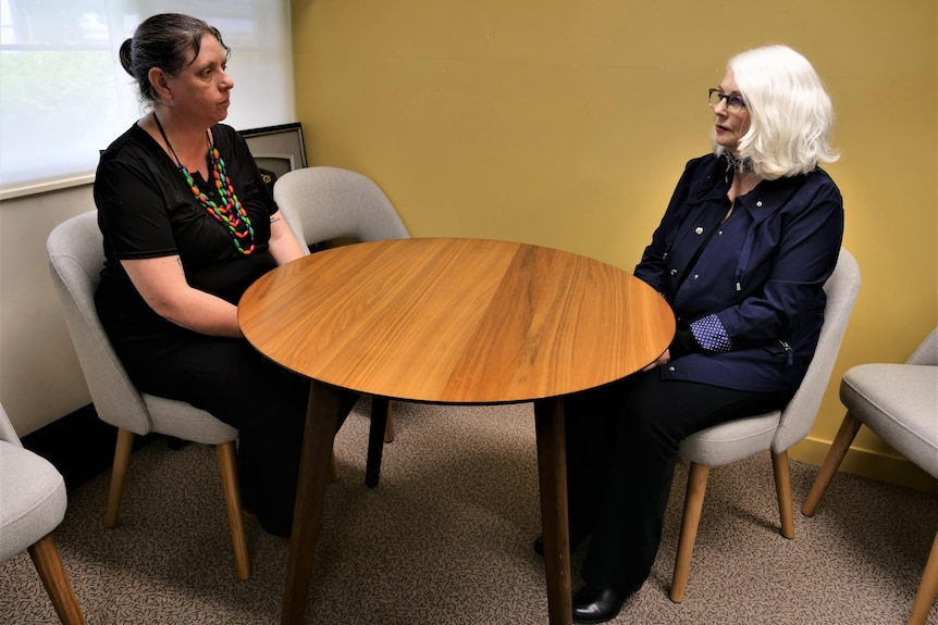 two women sit at an office table
