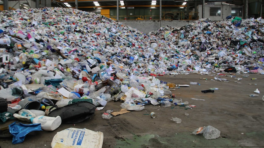 Large piles of waste such as plastic bottles and containers in a waste collection centre.