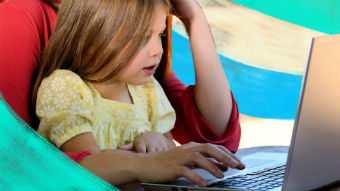 Young girl sitting on her mother's lap as the mum worked on a laptop.