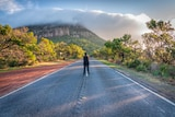 A man stands on a road at sunset. At the end of a road is a cloud-covered mountain.