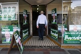 Barnaby Joyce has his back to the camera as he walks into his office with campaign posters stuck to the windows.