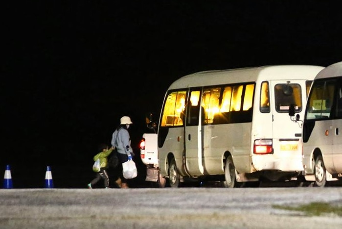 A long shot of a woman and a young boy walking towards a white bus at night with another bus behind it.