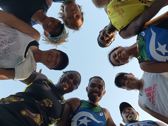 Members of the TI Deadly Runners stand in a huddle looking down at the camera.