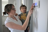 A woman is wearing glasses and looks at her air-conditioning controller on the wall with her young son on her hip.
