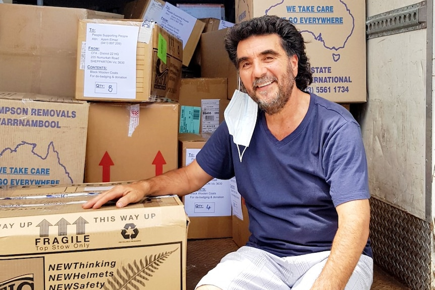 A man wearing sitting in the back of a truck filled with boxes.
