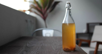 A bottle of kombucha on a table.