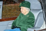 The Queen sits in a car wearing a green coat and a matching hat.