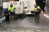 Two street cleaners wearing high vis clean a cobble stone laneway of spray paint.