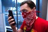 A man with a handkerchief over his mouth and nose looks fearfully at a smart phone.