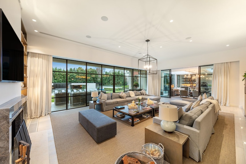 A large living space looking out to a lawn and swimming pool.