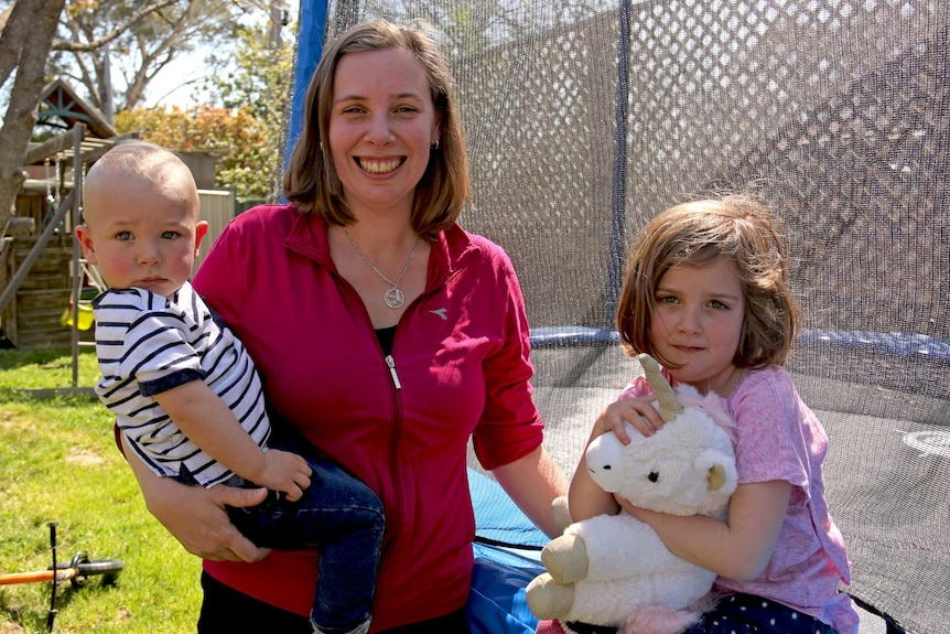 A woman in her backyard, holding her one-year-old son and next to her four-year-old daughter.