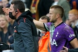 Eric Dier walks towards the pitch and points into the crowd next to a medic with a defibulator
