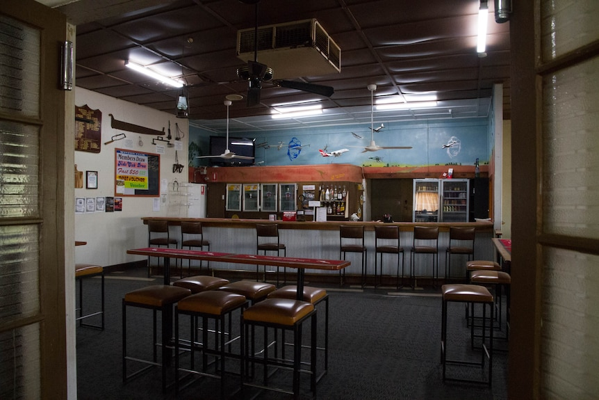 A dimly-lit bar room in a pub filled with airplane and Qantas memorabilia.