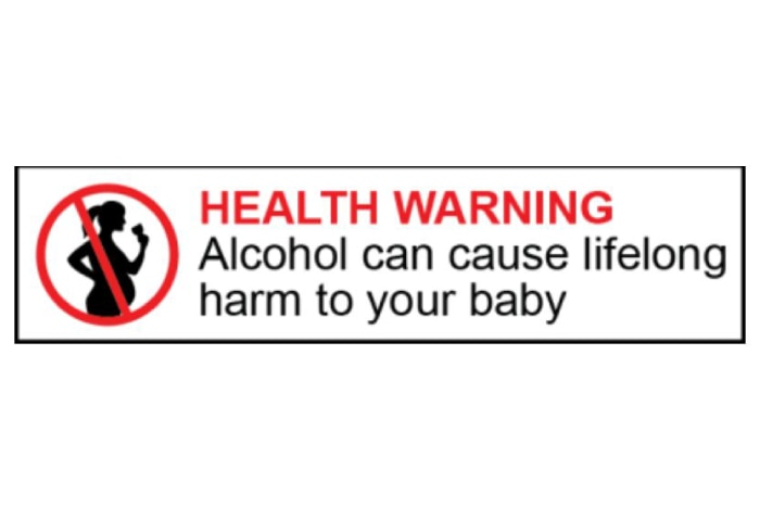 A label shows the silhouette of a pregnant woman drinking with the words HEALTH WARNING: Alcohol can cause lifelong harm to baby