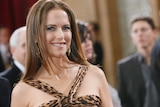 Kelly Preston wears a leopard print dress and smiles as she arrives at an awards ceremony.