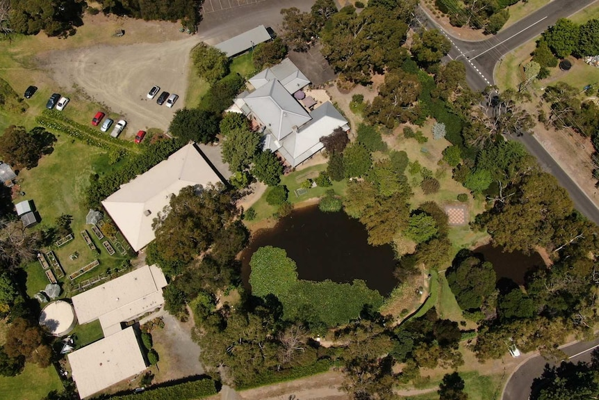 An aerial image of the The Ashram at Mt Eliza, showing several buildings, a gravel car park and two lakes and expansive gardens.