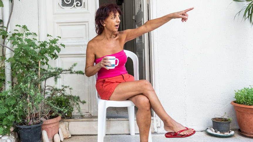 A woman in shorts and a tube top sits on her porch holding a cup with one hand and pointing with the other