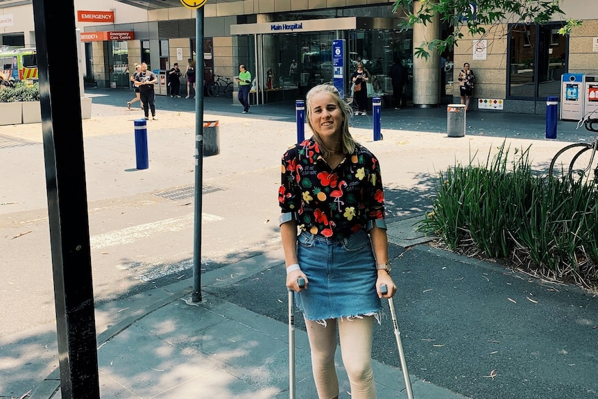A young woman wearing a black and red florat shirt, denim skirt and converse stands with crutches outside a hospital.