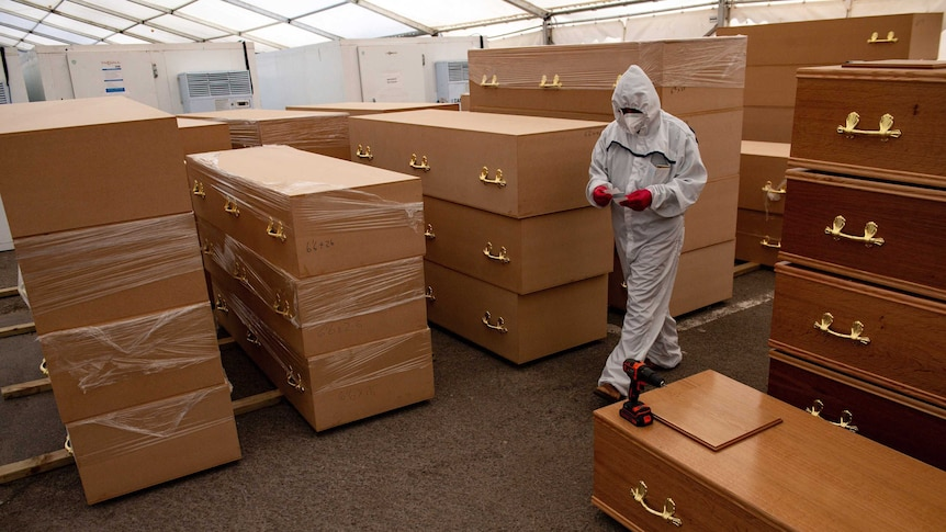A person in HAZMAT gear is surrounded by coffins as they walk through a makeshift morgue.
