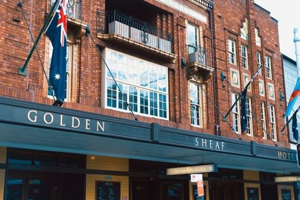 The exterior of a pub with the words Golden Sheaf Hotel on the awning.
