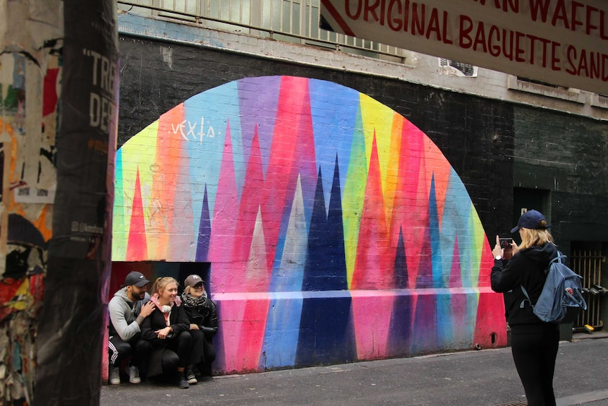 A woman takes a photo of three others in front of street art.