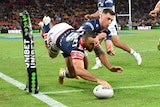 A Roosters player is mid-air as his hand plants the ball down in the corner for a try.
