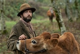 Film still of John Magaro as Cookie with a cow in First Cow
