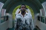 Yahya Abdul-Mateen II in a beaten-up and soiled white shirt lurches vacantly toward the camera, framed by a lime green archway.