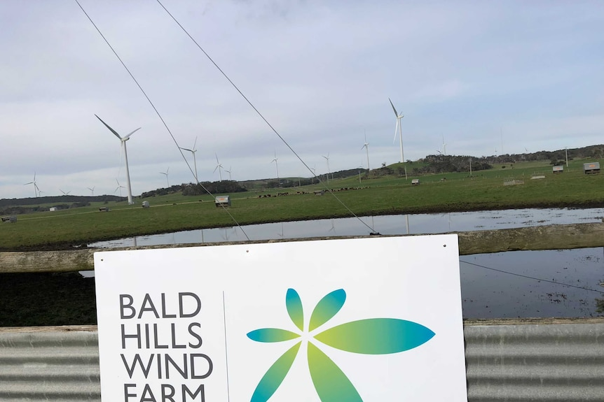 """A sign on a fence that says """"Bald Hills Wind Farm""""."""