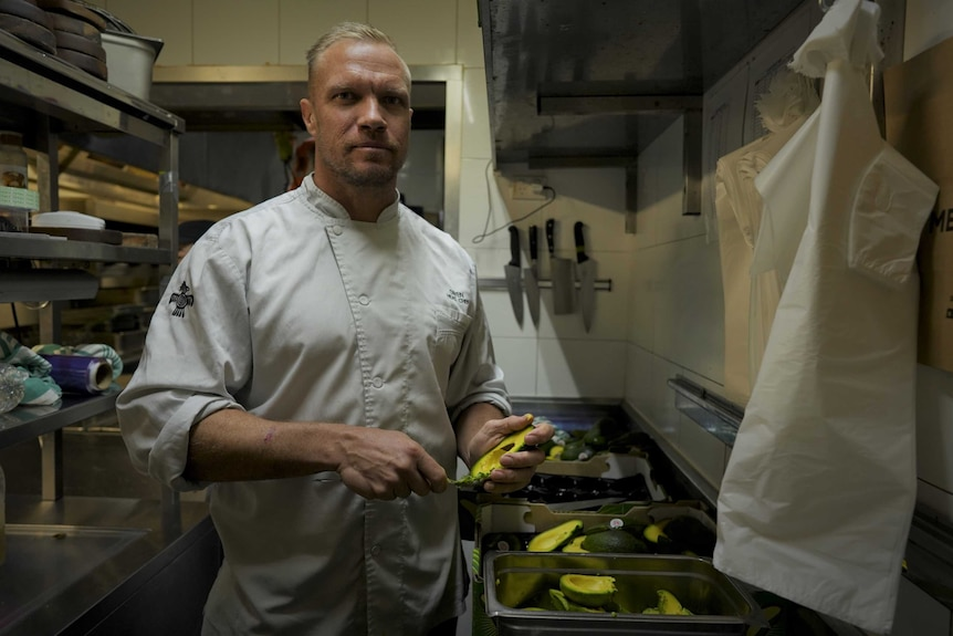 A cook stands in a commercial kitchen.