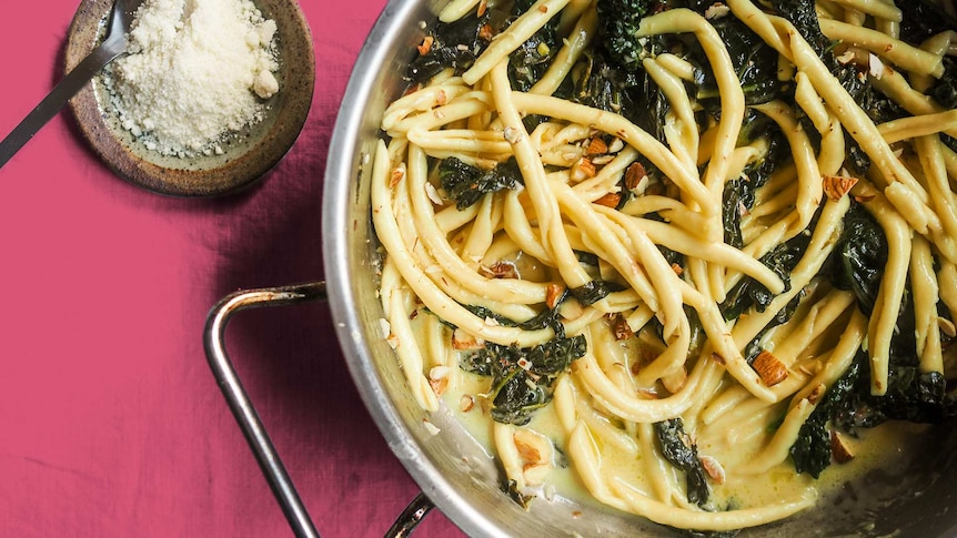 A close up of a pan filled with pasta, kale, cream, lemon and almonds, a quick dinner in one pan.