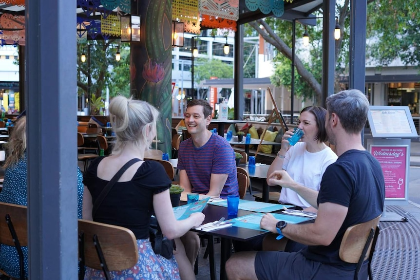 A group of people sit at a restaurant in Brisbane.